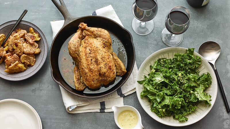 Whole roast chicken accompanied by dishes of crispy smashed potatoes and kale salad, with glasses of red wine