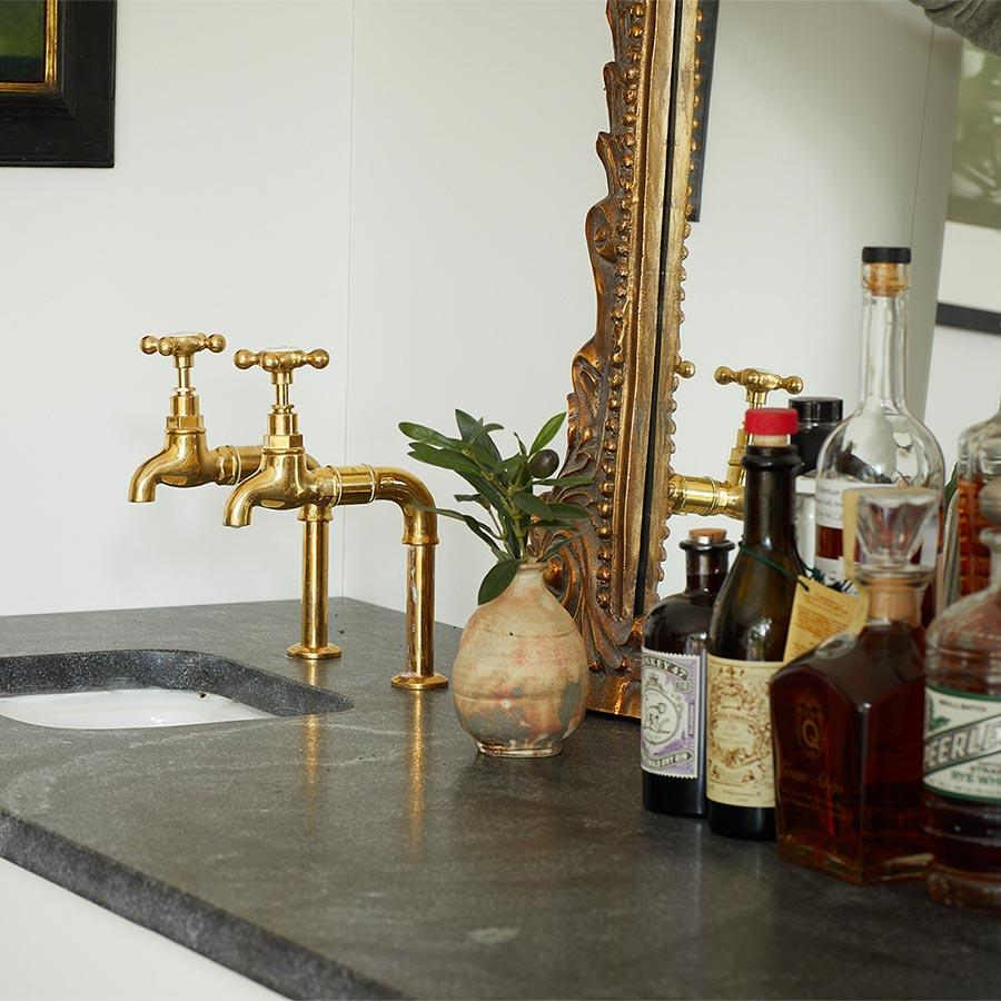 A wet bar with sink, brass-colored fixtures, an ornate mirror and liquor bottles. Photo by Ty Cole