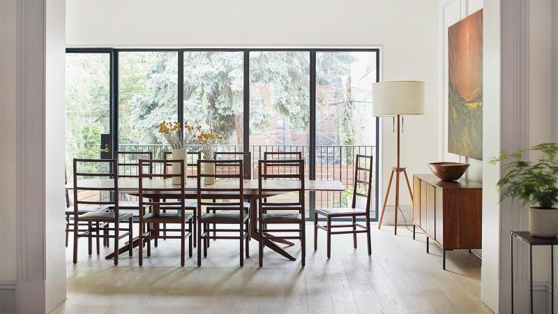 Light-filled dining room, with table in front of floor-to-ceiling windows. Photo by Ty Cole