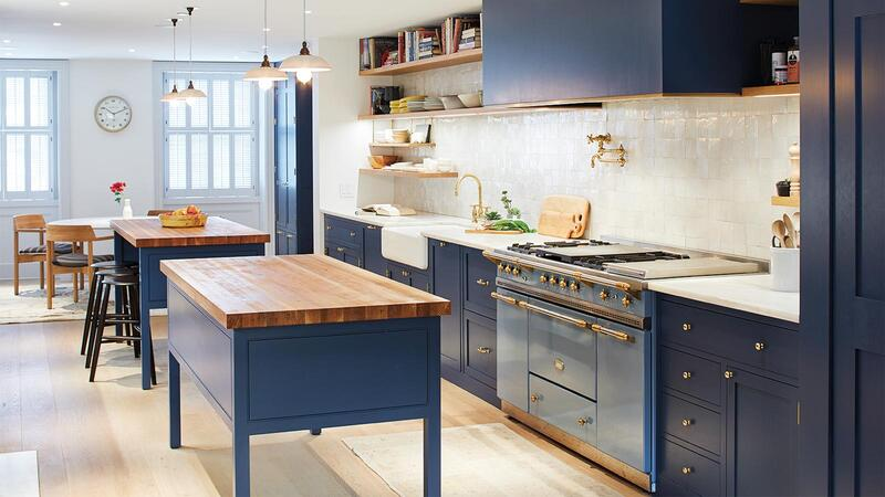 Kitchen with light-reflecting navy-blue walls and light oak floors.