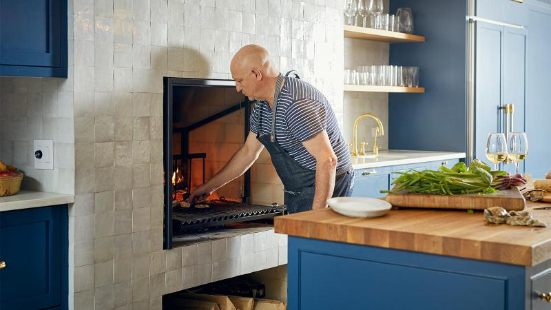 Tom Colicchio prepares a meal in front of an wood-burning grill in the kitchen. Photo by Ty Cole