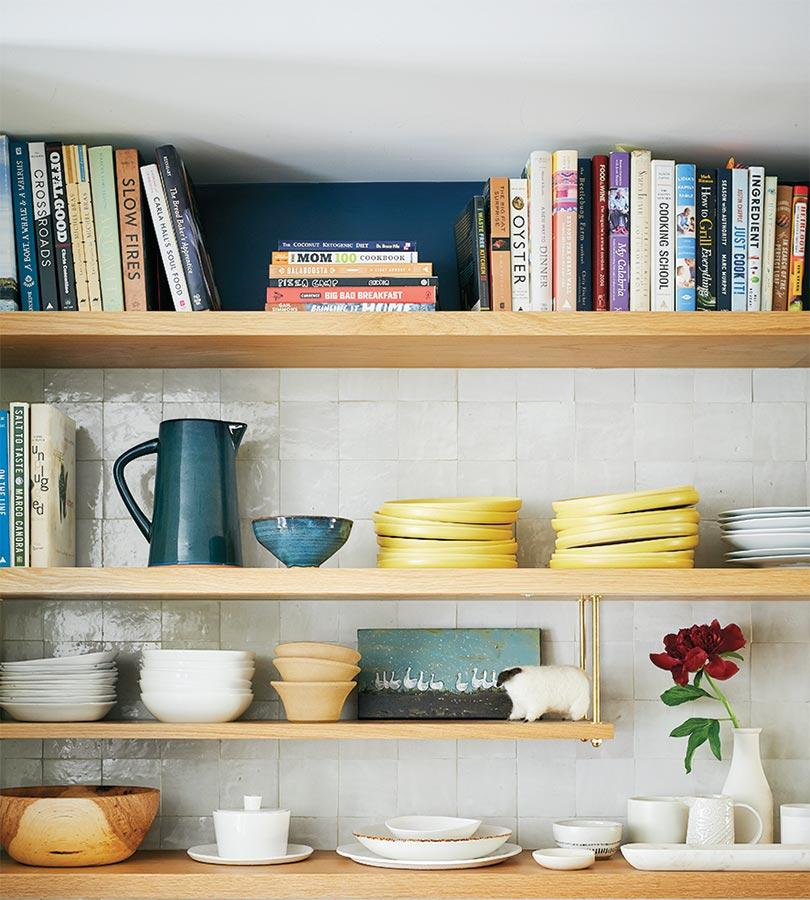 Exposed wood shelving stores a cookbook collection and dishware. Photo by Ty Cole
