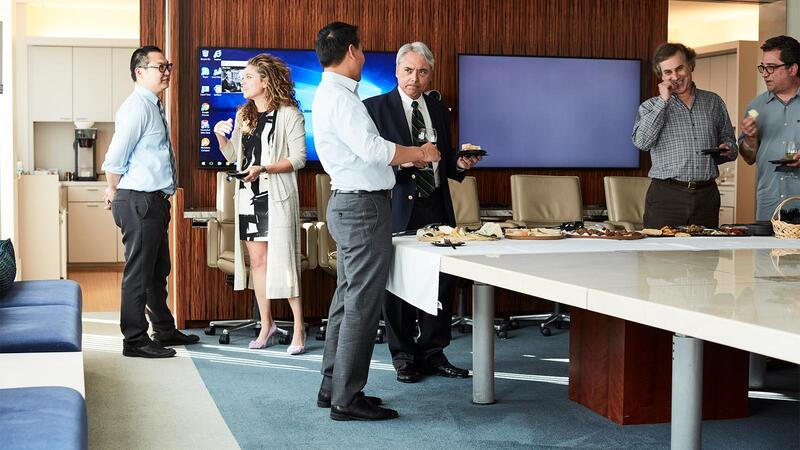 Junior and senior law firm employees mingle in a conference room over wine, plates of cheese and other food.