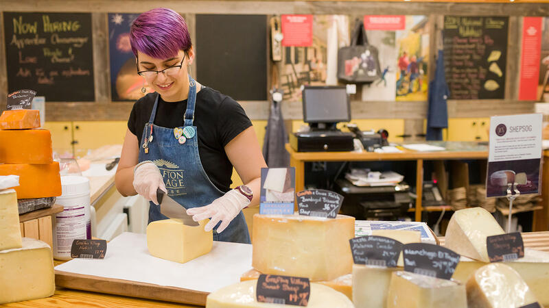 An employee cutting cheese at Grafton Village Cheese Co.