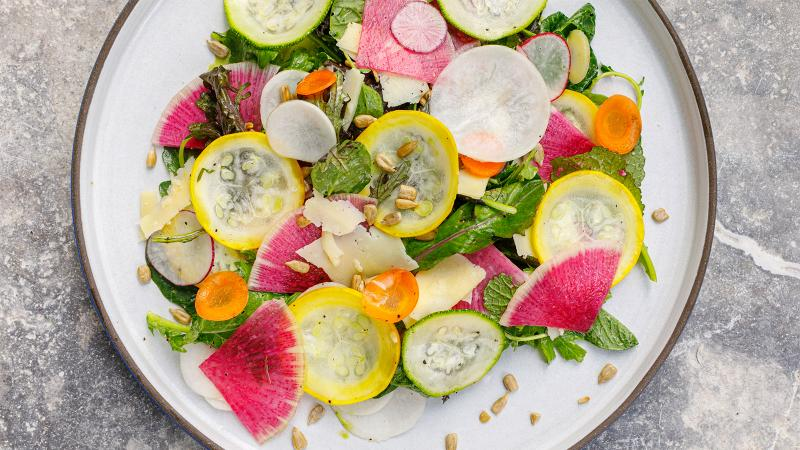 A colorful salad with green and yellow zucchini, radishes, carrots and sunflower seeds