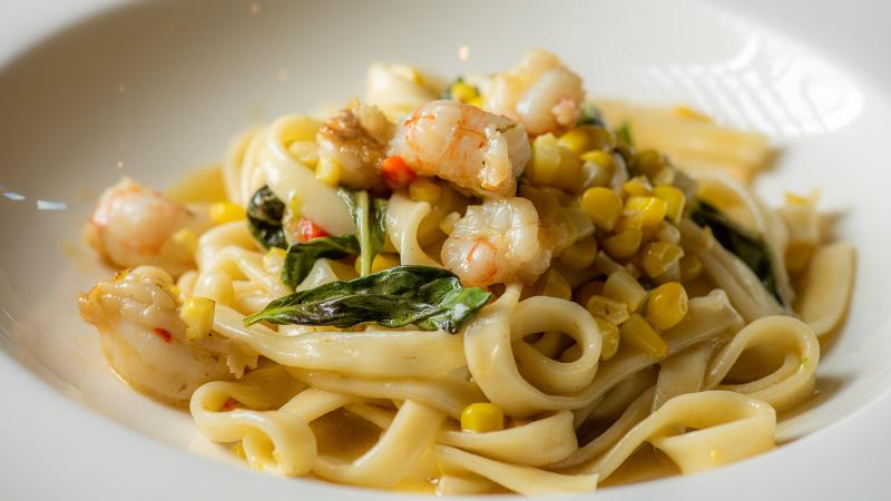 Flat pasta noodles with shrimp and corn