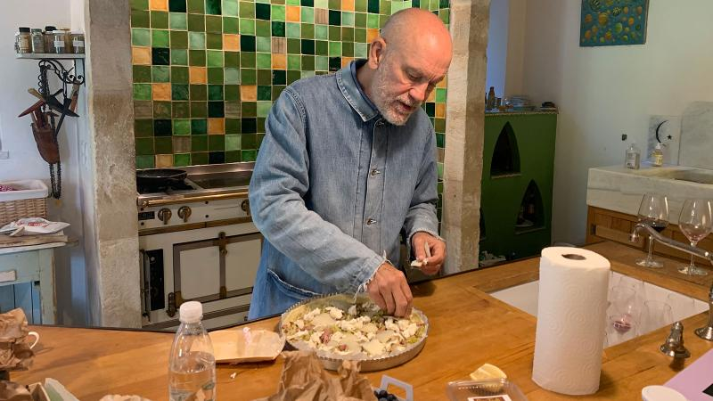 Actor John Malkovich preparing a vegetable tart in his French estate's kitchen