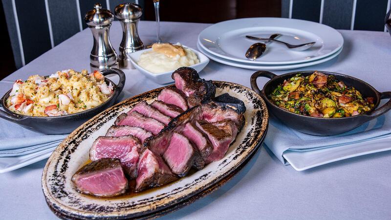 A steak-and-sides spread with red wine at Blackstone Steakhouse
