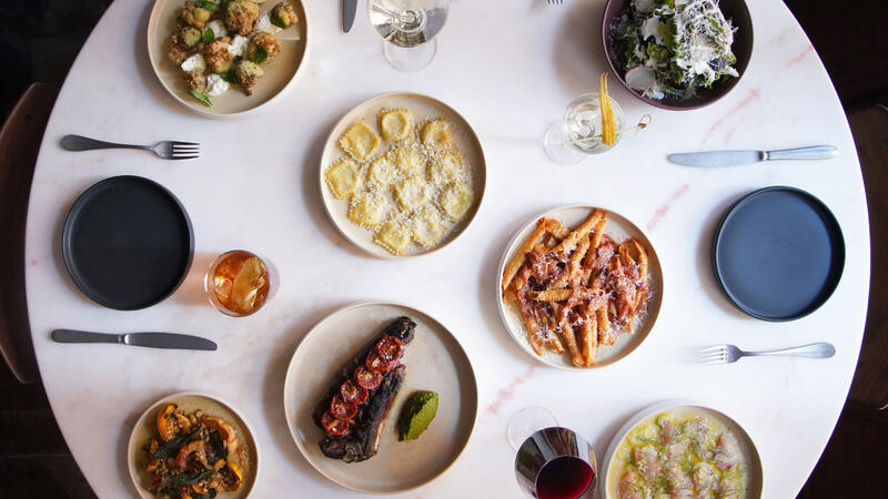 An overhead view of dishes and wine at Via Locusta