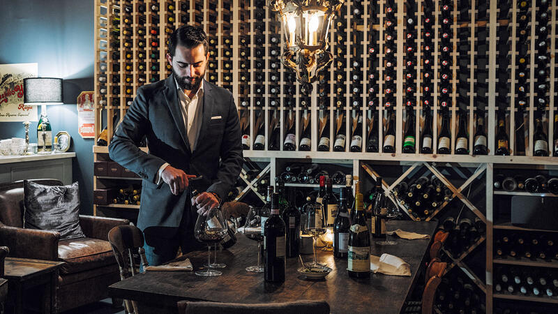 Wine director Andrey Tolmachyov opening a bottle in Maude's cellar