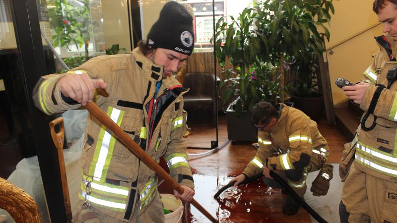 Firemen cleaning up wine spill