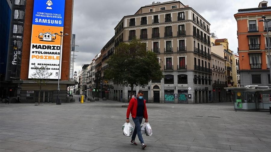 A lone man walks through a Madrid plaza as Spain continues a broad shutdown to combat COVID-19.