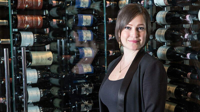 Wine director Rachael Lowe in front of Spiaggia's wine display