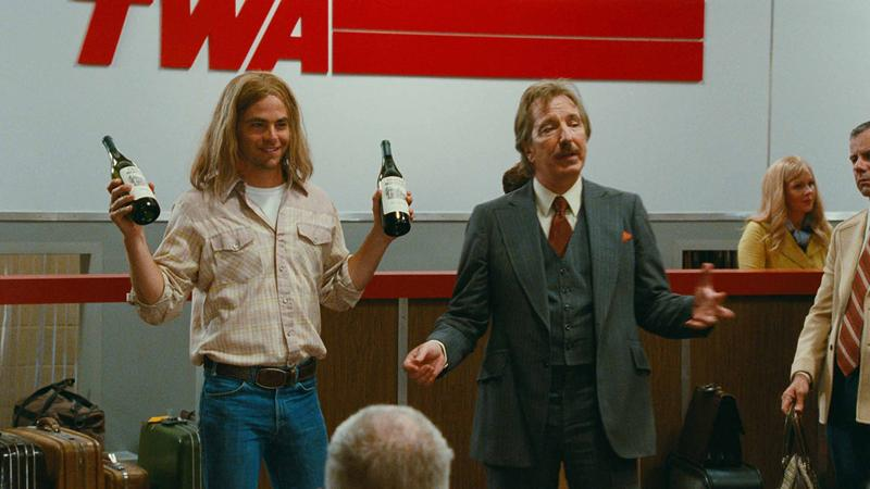 Bo Barrett (Chris Pine), holding up wine bottles, and Stephen Spurrier (Alan Rickman) at the TWA checkin counter