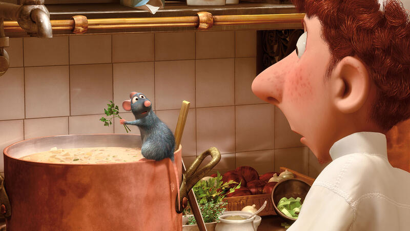 Remy the rat adds herbs to a pot of soup as the astonished dishwasher Linguini looks on
