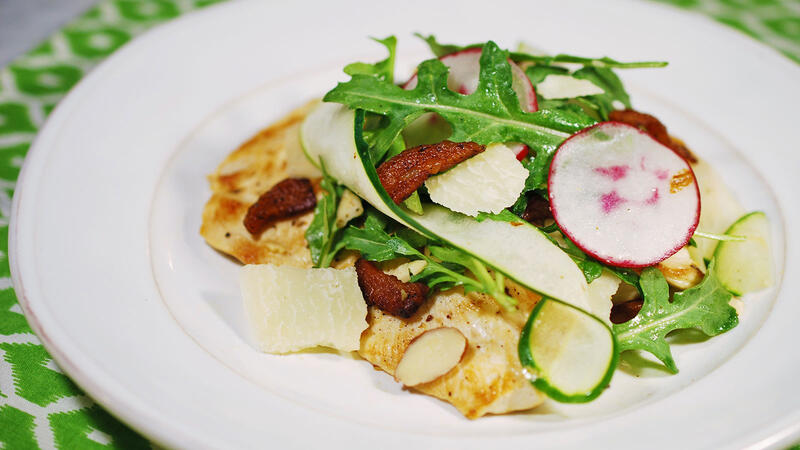 Pan-cooked chicken topped with salad of arugula, radishes, shaved cucumber, toasted almonds and shaved parmesan