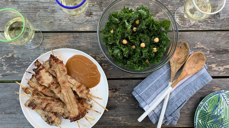 Overhead shot of a plate of pork satay skewers with peanut sauce, a bowl of kale and chickpea salad and glasses of white wine on a weathered wood outdoor table.