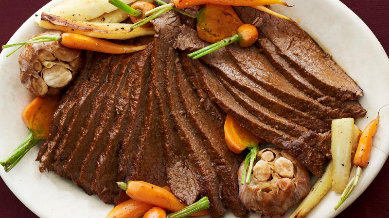 A platter of sliced beef brisket accompanied by baby carrots and roasted garlic