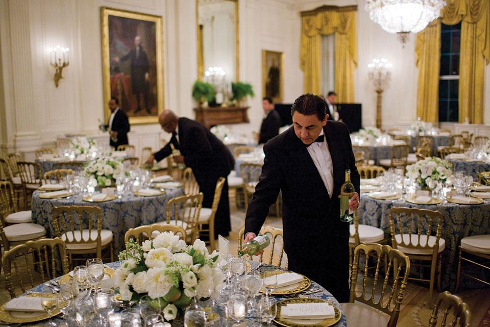 White House butlers pour white wine in the East Room before a dinner for congressional committee chairs in 2009.