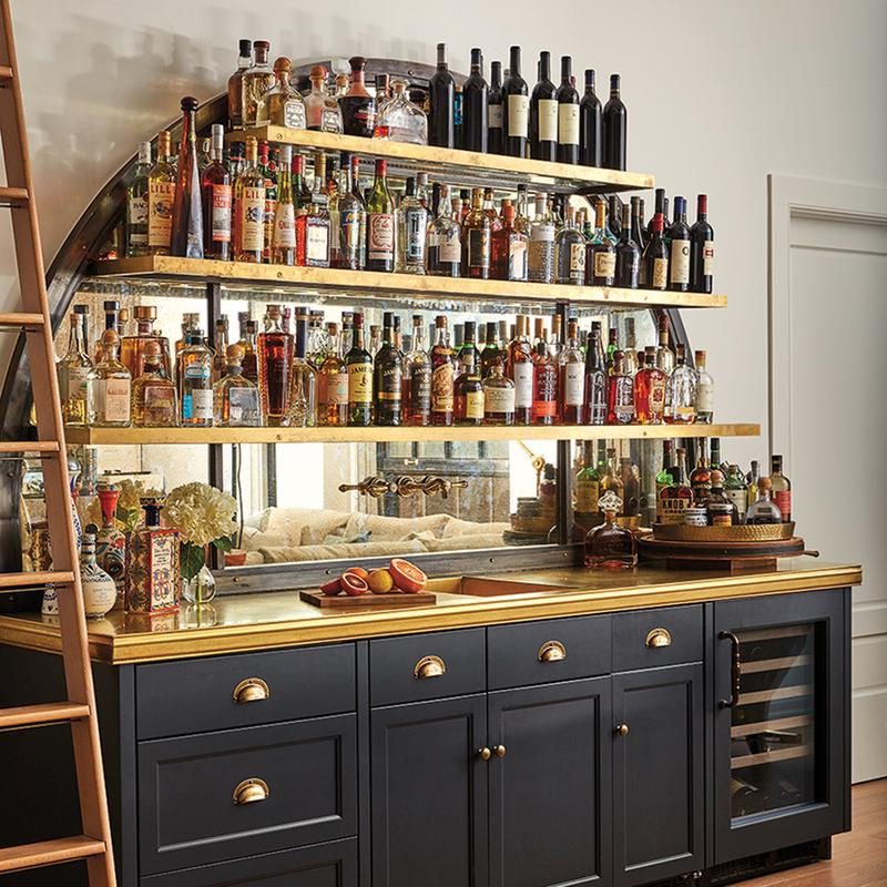 Navy-and-brass home bar with three shelves of wine and spirits bottles, countertop with sink and cabinets holding wine coolers