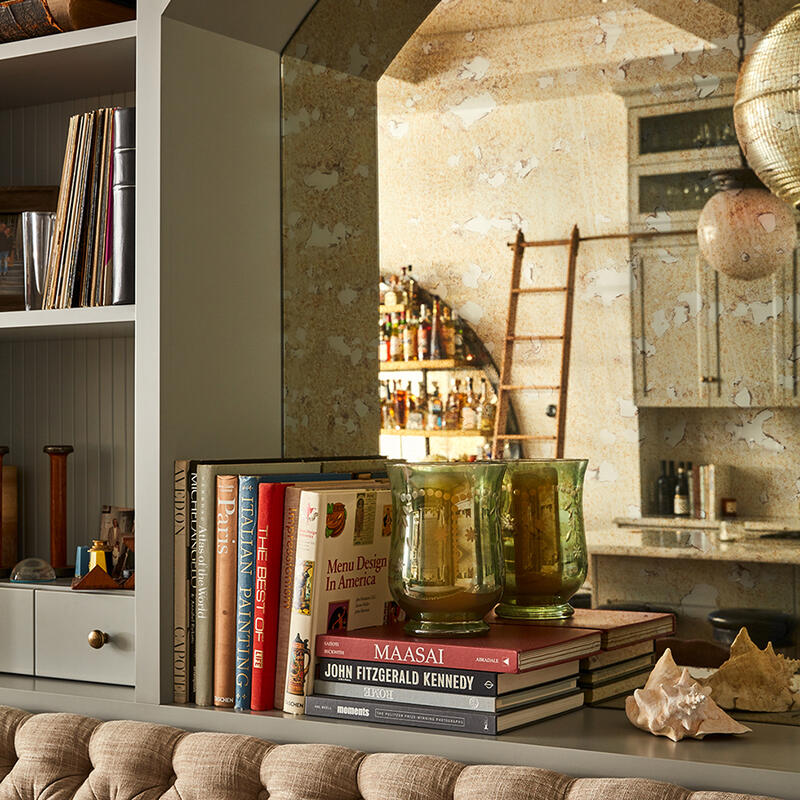 Bookshelves and mirrored wall recess, displaying cookbooks, reference books and art objects above a banquette