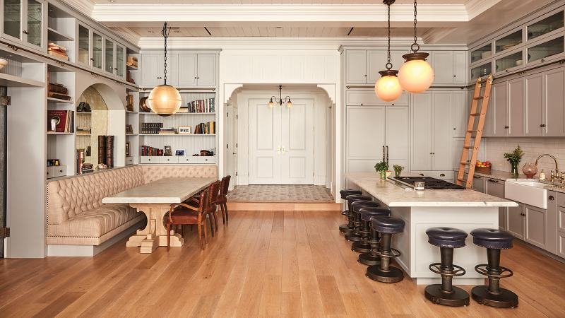An open white, beige and taupe kitchen with high ceilings, globe pendant lamps, floor-to-ceiling custom cabinets, a dining banquette on the left and counter with bar stools on the right