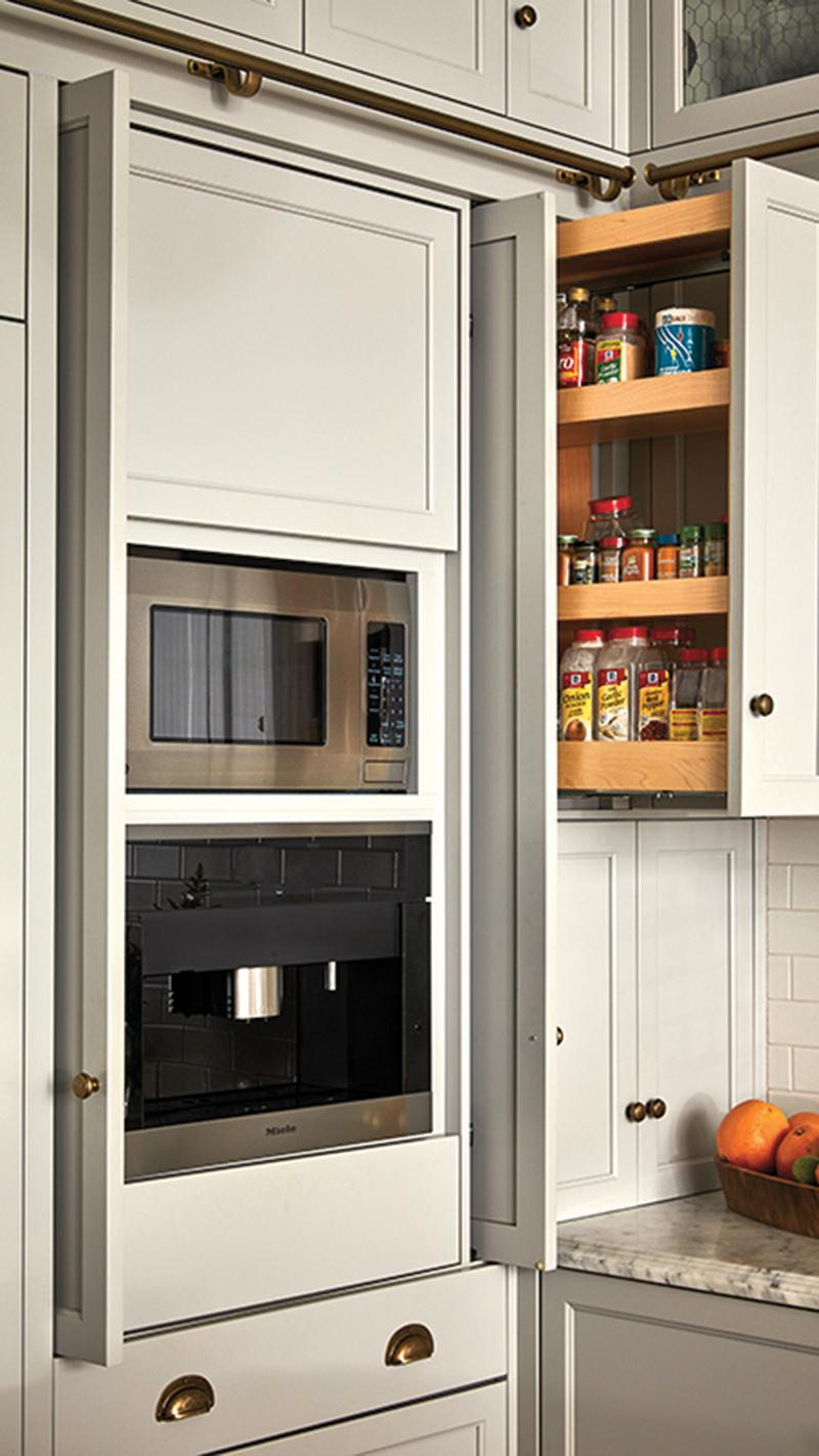 White kitchen cabinets with a pull-out spice rack next to the microwave and toaster oven