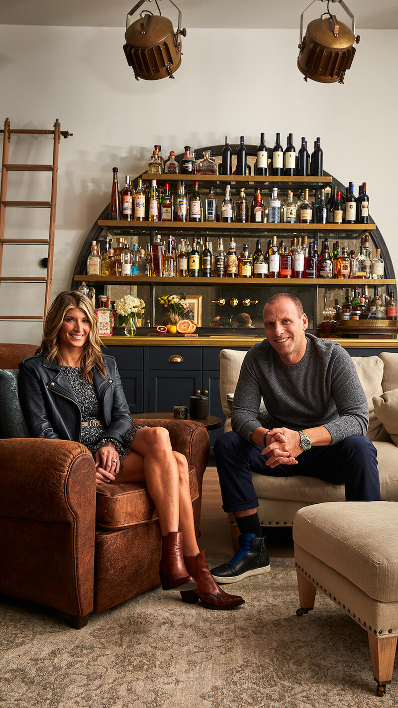 Portrait of Nina Tinari (left) and Michael Schulson in their open-plan living room, seated in front of their bar