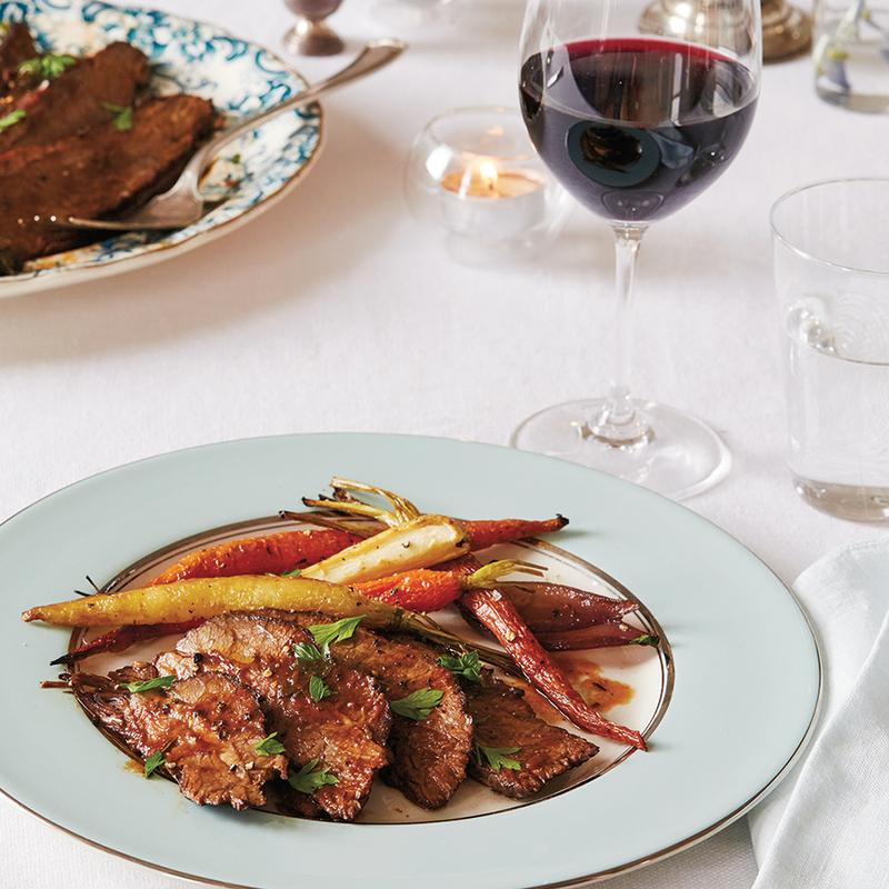 Plate of sliced brisket with roasted root vegetables and a glass of red wine