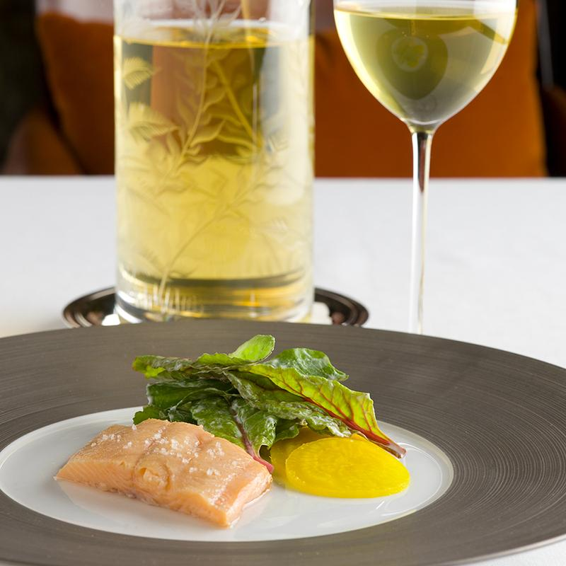 Appetizer of smoked trout with yellow beets and greens, accompanied by a glass and carafe of white wine