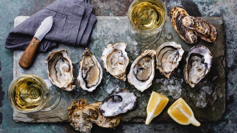 Raw shucked oysters and glasses of wine