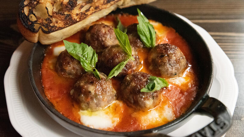 Cheesy meatballs with fresh basil and a slice of toasted bread at Monarch