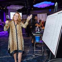 Gina Gallo, glass of red wine in hand, checks out the map of the Grand Tastings