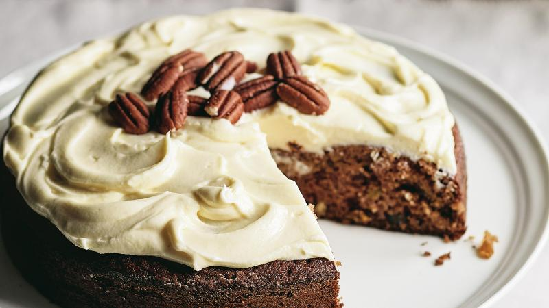 A cream-cheese-frosted, nut-topped bourbon applesauce cake with a slice cut out